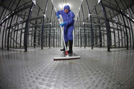 pulizia pavimenti: lavoratore in protezione pulizia del pavimento uniforme in magazzino vuoto - eye pesce