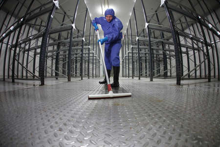 dry cleaner: worker in protective  uniform cleaning floor in empty storehouse - fish eye lens