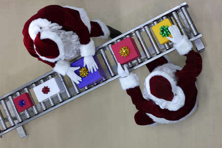 commercialization: overhead view of two santa clauses working at production line in presents factory