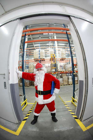 commercialization: santa claus in red helmet at the gate to storehouse full of goods