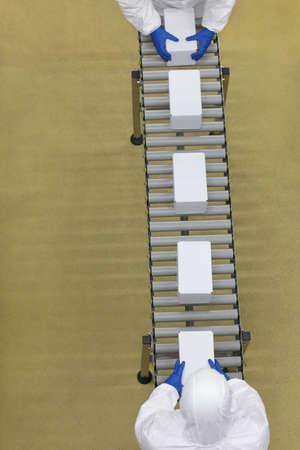 cinta transportadora: Vista aérea de dos trabajadores en los uniformes blancos de trabajo con las cajas de embalaje en línea Foto de archivo