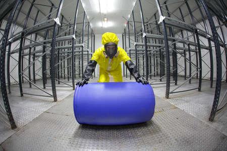 sustancias toxicas: totalmente protegido en uniforme amarillo, m�scara, guantes de goma y t�cnico, rodando el barril con la sustancia t�xica en el almac�n vac�o - lente ojo de pez Foto de archivo