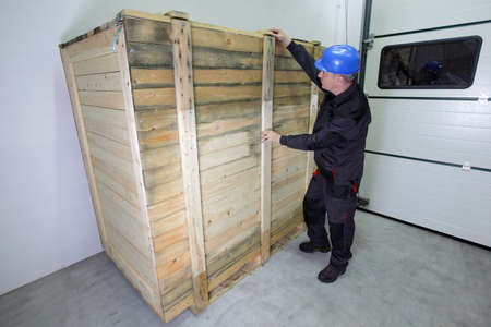 industrial worker in hardhat and uniform checking large wooden box photo