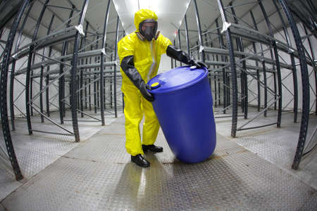 hazardous: Worker in protective uniform,mask,gloves and boots rolling barrel of chemicals in empty storehouse - fish eye lens
