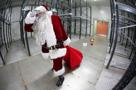 The last,tired Santa Claus loosing gifts from red sack leaving empty storehouse photo