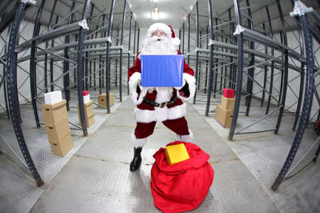 commercialization: Santa Claus preparing for Christmas,showing gift  in empty storehouse, fish-eye photo Stock Photo