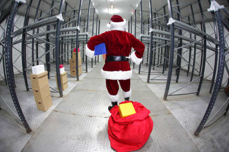 irony: Late Santa Claus preparing for Christmas in empty storehouse Stock Photo