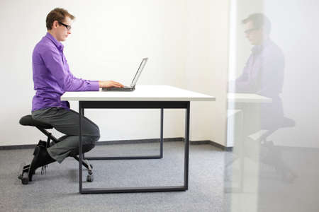 proper: correct sitting position at workstation  man on kneeling chair Stock Photo