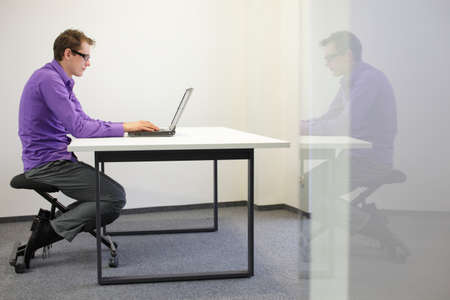 wrong: bad sitting posture at workstation  man on kneeling chair