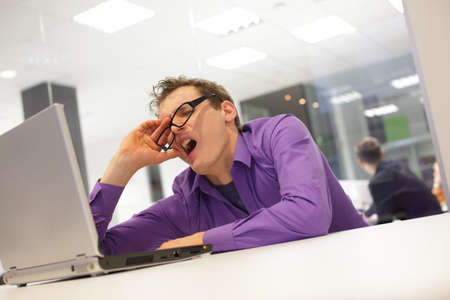 yawn: bored yawning businessman working with laptop supporting his head on his hand in office space