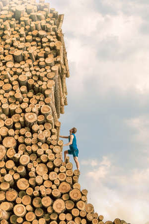 pile of logs: Challenge - Young man climbing the large pile of cut wooden logs Stock Photo