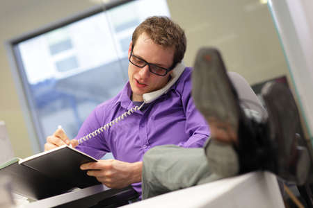 ergonomic: Young businessman caucasian in his office on phone making notes - bad sitting posture Stock Photo