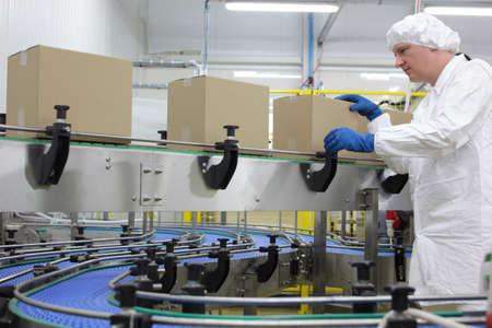 manufactura: cauc�sico trabajador hombre en delantal blanco, gorro y guantes azules en la l�nea de embalaje en f�brica
