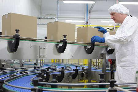production plant: caucasica uomo lavoratore in grembiule bianco, berretto e guanti blu alla linea di confezionamento in fabbrica