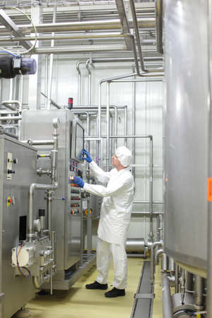 Technician in white uniform,cap and blue gloves, controlling industrial process in factory photo