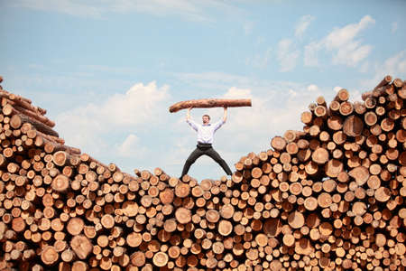 will power: man on top of large pile of logs, shouting, lifting heavy log