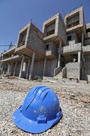 speculation: broken hard hat and unfinished apartments in background - crisis in development industry Stock Photo