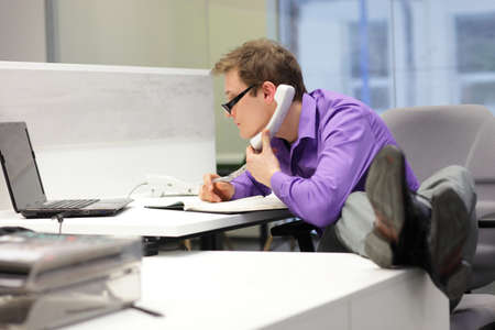 bad habits: businessman on phone looking at screen of laptop - bad sitting posture Stock Photo