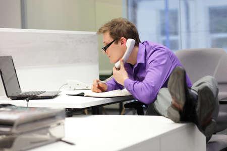 ergonomics: businessman on phone looking at screen of laptop - bad sitting posture Stock Photo