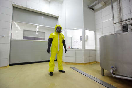 professional in protective uniform standing in industrial environment photo