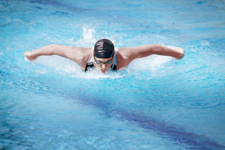swimmers:  Swimmer in competition swimwear performing the butterfly stroke