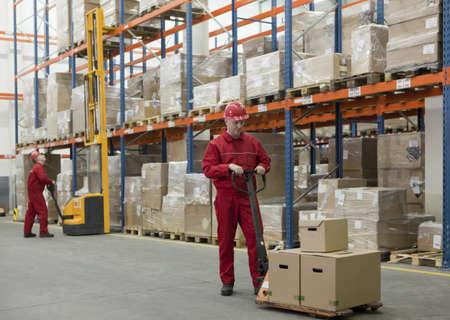 palet: almacenamiento - dos trabajadores en los uniformes y cascos de seguridad de trabajo en el almacén