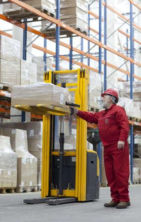 storeroom: warehousing  -  Senior worker in red uniform with bar code reader in warehouse
