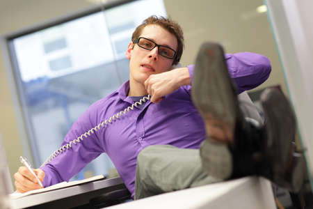 bad sitting posture - Young businessman caucasian in his office on phone making notes photo