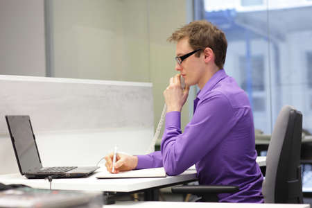 back straight: Young businessman caucasian in his office on phone making notes Stock Photo