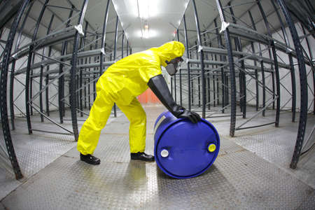 hazardous waste: fully protected in yellow uniform,mask,and rubber gloves technician,rolling the barrel with toxic substance in empty warehouse - fish eye lens  Stock Photo
