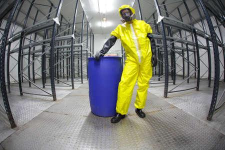 residuos toxicos: trabajador en materia de seguridad - protecci�n uniforme, de pie en azul barril - retrato Foto de archivo