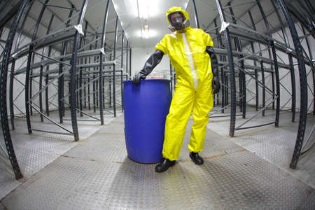 hazardous waste: worker in safety - protective uniform,standing at blue barrel - portrait  Stock Photo