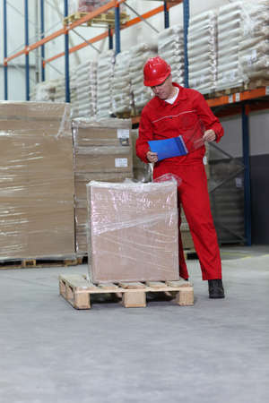 order shipment: A worker checking inventory stocks at a factory storeroom  Stock Photo