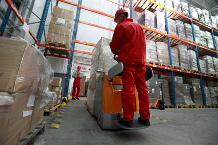 human chain: logistics - goods delivery - two workers working in storehouse with forklift loader