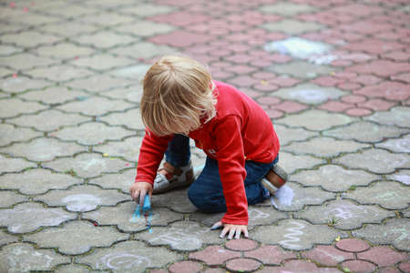 Preschooler child drawing with chalk on sidewalk photo