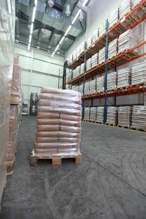 Sacks on wooden pallet inside storehouse