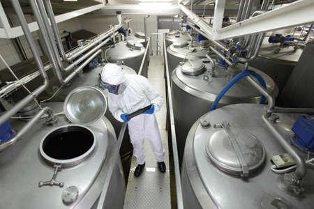 biotecnologia: Técnico en uniforme protector y máscara con la tableta controlar el proceso tecnológico en la planta de