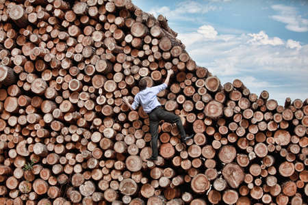 hardworking:  Challenge- businessman climbing the large pile of logs