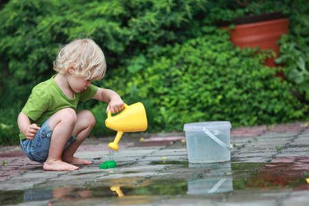 Weiße kleine Mädchen barfuß spielen mit Wasser