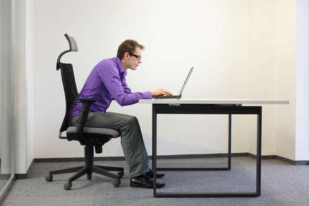 나쁜 노트북에 앉아있는 자세. 의자에 사람