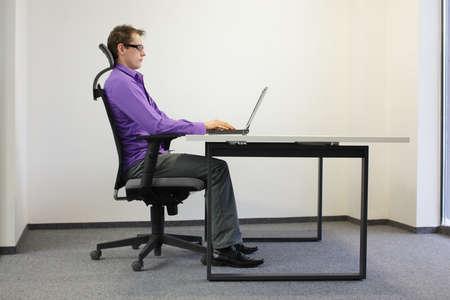ワークステーションで座っている位置を修正します。ノート パソコンで作業の椅子の上の男 写真素材