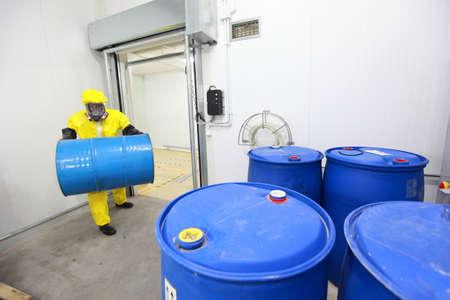 chemical risk: Trabajador en uniformes de protección, mascarilla, guantes y botas que llevan barril de productos químicos Foto de archivo