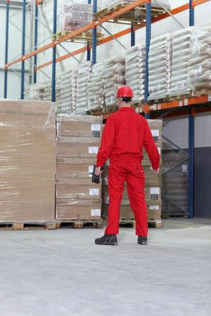 bar code reader: trabajador en uniforme rojo con lector de c�digo de barra de la preparaci�n para el trabajo en almac�n Foto de archivo