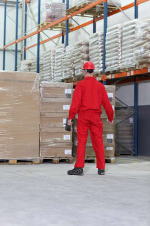 cellophane: worker in red uniform with bar code reader preparing to work in warehouse