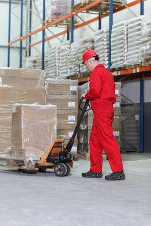 carretillas almacen: trabajador en uniforme rojo en el trabajo con la mano toma transpaleta el?ctrica en almac?n