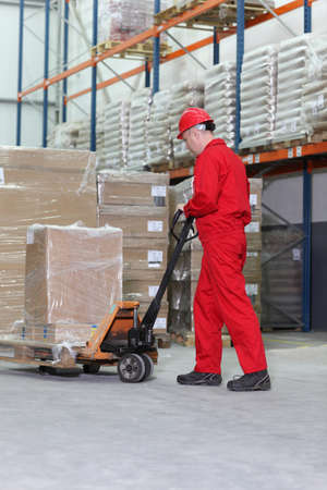 forklift truck: worker in red uniform at work with hand powered pallet jack in warehouse