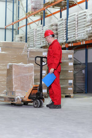 inferior: worker in red uniform at work with hand powered pallet jack in warehouse
