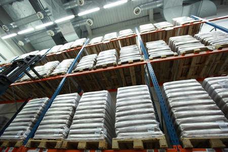 Sacks on wooden pallets on shelves  inside storehouse Stock Photo