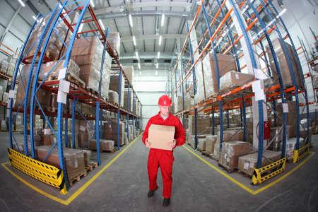 inventory: Trabajador en uniforme rojo con el rect�ngulo en el almac�n de la lente de ojo de pez Foto de archivo