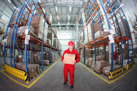 warehouse interior: worker in red uniform with box in the warehouse in fish-eye lens